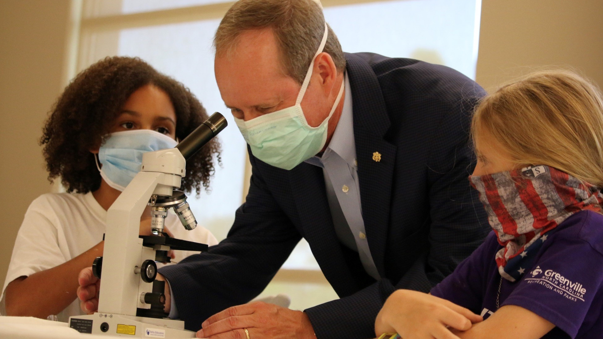 Congressman Murphy examining a microscope with some students from eastern North Carolina.